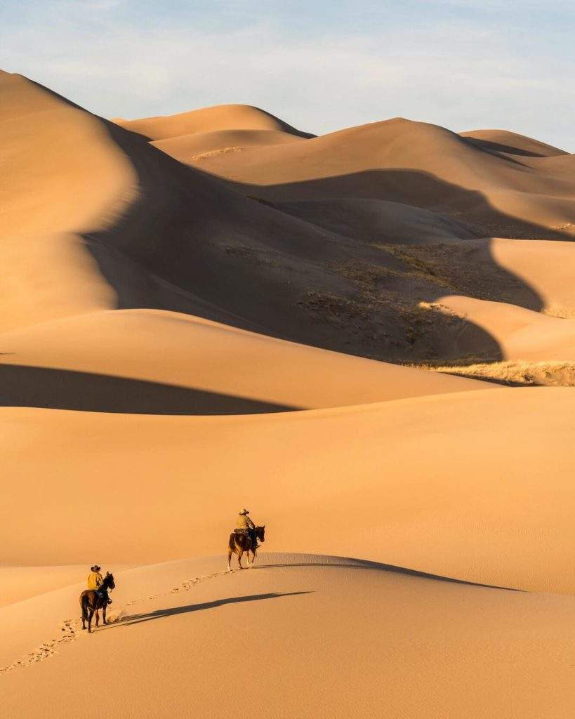 Riding horse back across sprawling yellow sand dunes