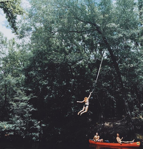jungle woman swinging from vine harasses canoers