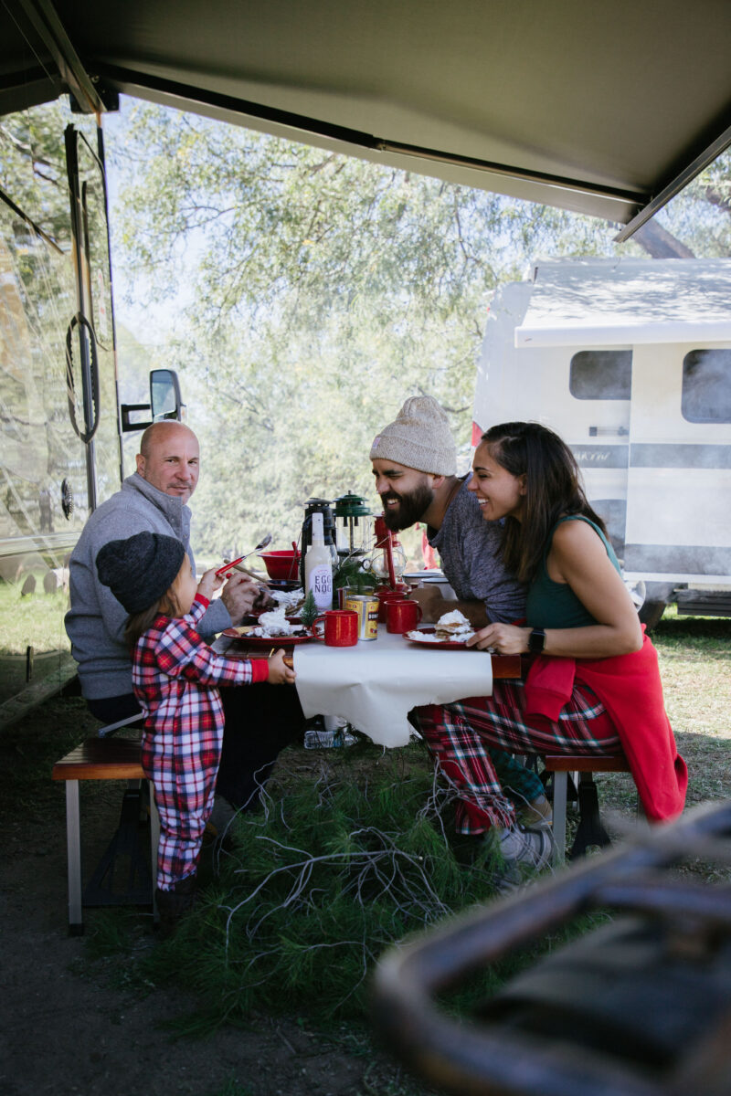 RVing family enjoying Christmas morning breakfast at their campsite