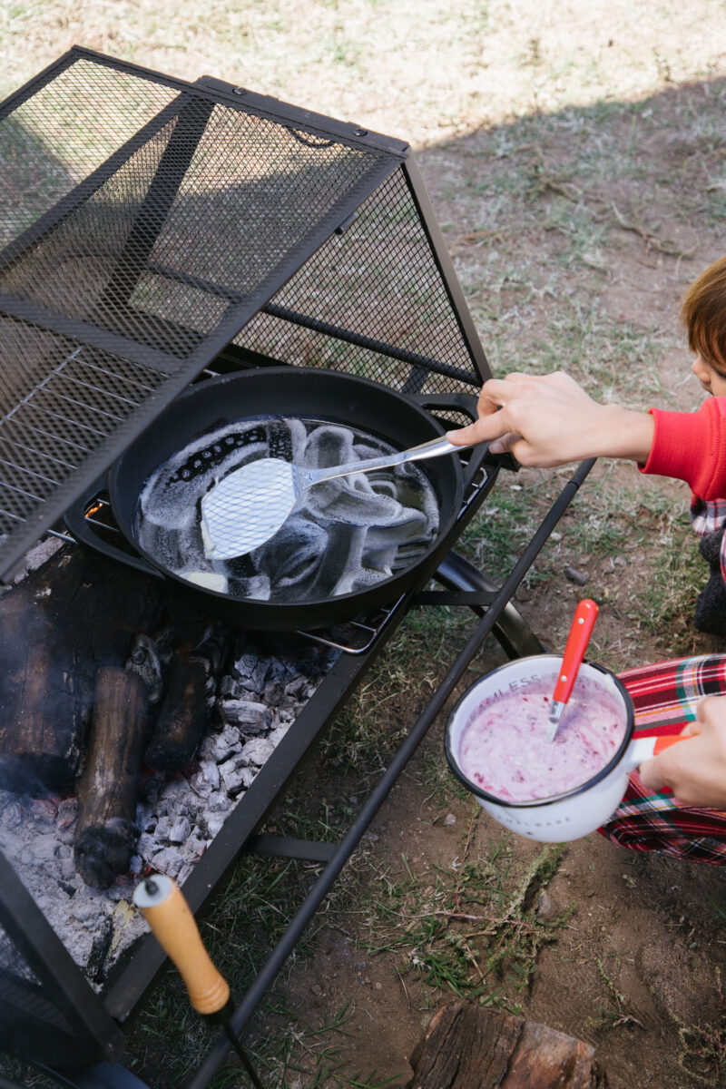 Cooking pancakes over the campfire grill on Christmas morning
