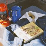 Vintage camping gear: lantern, kettle, wilderness book and sherpa jean jacket
